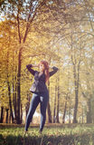 Beautiful woman with red hair in autumn park Stock Photos