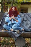 Beautiful Woman with red hair in the autumn park. sitting on a bench with a veil and covering her face with a book. Autumn backgro. Woman with red hair in the royalty free stock photos