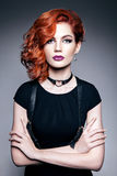 Beautiful woman with red hair in a black dress Stock Photography