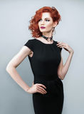 Beautiful woman with red hair in a black dress Royalty Free Stock Photos