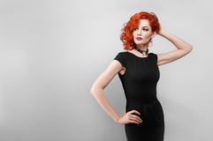 Beautiful woman with red hair in a black dress Royalty Free Stock Images