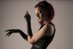 Beautiful woman with red hair and black paint on hands Royalty Free Stock Image