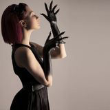 Beautiful woman with red hair and black paint on hands. Beautiful elegant woman with red hair and black hands Stock Photography