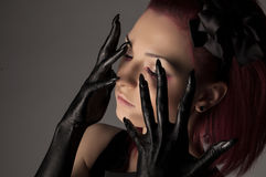 Beautiful woman with red hair and black paint on hands Royalty Free Stock Photo