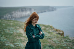 Beautiful woman with red hair on a cliff of a mountain near the sea, wind, sadness Stock Photos