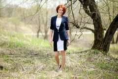Beautiful woman with red hair posing outdoors Stock Image