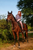 Woman with red hair sitting on a horse Stock Photo