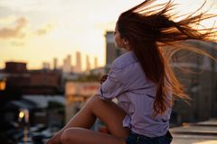 Beautiful Woman with red hair sitting on a roof or bridge, sunset light. Beautiful Woman with red hair sitting on a roof or bridge, summer outdoors stock photo