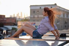 Beautiful Woman with red hair sitting on a roof or bridge, sunset light. Beautiful Woman with red hair sitting on a roof or bridge, summer outdoors royalty free stock image