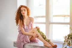 Beautiful woman with red hair sitting at the window with flowers, spring mood.  stock photography