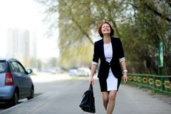 Beautiful woman with red hair on the street. Beautiful woman with red hair in business suit walking down the street Stock Image