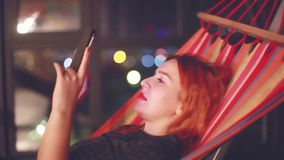 Beautiful woman with red hair using smart phone mobile in the city at night liying in hammock. 1920x1080. Woman using smart phone mobile in the city at night stock video footage