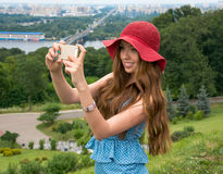 Beautiful woman in a red hat taken picture of herself, selfie. Stock Image