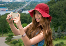 Beautiful woman in a red hat taken picture of herself, selfie. Royalty Free Stock Photography