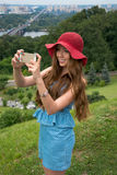Beautiful woman in a red hat taken picture of herself, selfie. Stock Photos