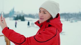Beautiful woman in a red jacket makes a selfie in winter stock footage
