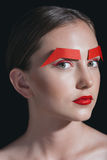 Beautiful woman with red lips and paper brows posing for fashion shoot isolated on black Stock Images