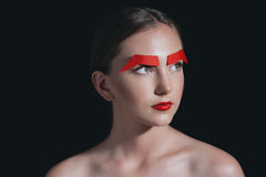 Beautiful woman with red lips and paper brows posing for fashion shoot isolated on black Stock Photography