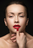 Beautiful Woman with red lips touching her Lips. Stock Photos