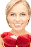 Beautiful woman in red mittens with snow Stock Image