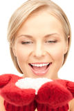 Beautiful woman in red mittens with snow Stock Photos