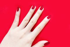Beautiful Woman Red Nail. Female Hand with Red Nails Manicure  on the Red Fabric Background. Great for Any Use Royalty Free Stock Images