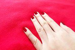 Beautiful Woman Red Nail. Female Hand with Red Nails Manicure  on the Red Fabric Background. Great for Any Use Stock Photography