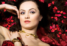 Beautiful woman in red petals Royalty Free Stock Image