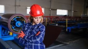 Beautiful woman in red safety helmet work as industrial worker. At metal sheet profiling mechine at manufacturing factory Royalty Free Stock Photos