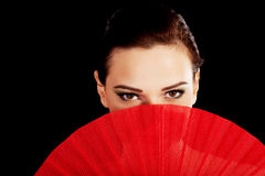 Beautiful woman in red sexy dress with fan. Royalty Free Stock Photo