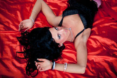 Beautiful woman on red silk stock photography