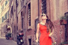 Beautiful woman in red summer dress walking smiling in Rome, Italy royalty free stock image