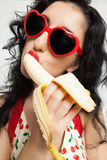 Beautiful woman with red sunglasses sexy eating banana Stock Image