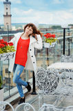 Beautiful woman in a red sweater posing near the rails Stock Image