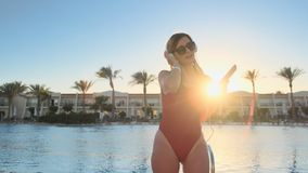 Beautiful woman in red swimsuit and headphones, dancing and listening music on smartphone. Portrait of bikini girl in stock video footage