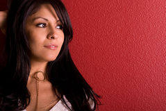 Beautiful woman by red wall. Latina standing by a red wall, she is looking to the side stock image