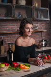 Beautiful woman with red wine glass sitting in kitchen vegetables on table. Royalty Free Stock Image