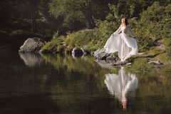 Beautiful woman reflected in alpine lake Royalty Free Stock Photo
