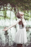 Beautiful woman rejoicing in the joys of nature. Beautiful young woman in a fresh white summer dress standing with her arms outspread rejoicing in the joys of Stock Photography