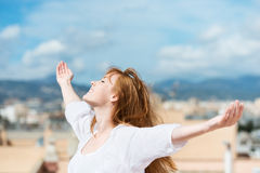 Beautiful woman rejoicing in the sunshine. Standing with her arms outstretched and her head tilted to the sun Stock Image
