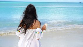 Young woman with cup of hot drink on white tropical beach. SLOW MOTION. Back view of girl enjoying the beautiful sea. Beautiful woman relax during exotic stock footage