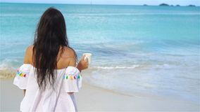 Young woman with hot coffee on white tropical beach. SLOW MOTION. Beautiful woman relax during exotic vacation on the beach enjoying sweet coffee stock footage