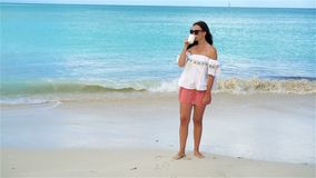 Young woman with hot coffee on white tropical beach. SLOW MOTION. Beautiful woman relax during exotic vacation on the beach enjoying sweet coffee stock video footage