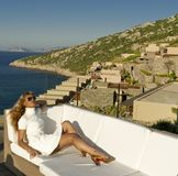 Beautiful woman relax on the white sofa near coast Stock Image