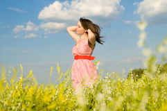 Beautiful woman relaxation. The beautiful young woman in a field, on the nature, dreams, is happy, hair are inflated with a wind Royalty Free Stock Image
