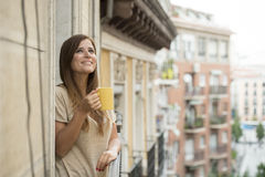 Beautiful woman relaxed cheerful drinking tea coffee at apartment balcony terrace. Young beautiful woman on her 30s relaxed and cheerful drinking hot tea or royalty free stock photo