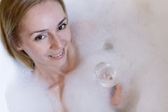 Portrait of a Happy Woman in a Bathroom with Wine. Beautiful Woman Relaxes in the Bathroom with a Glass of Wine royalty free stock photos