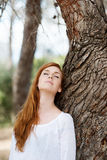 Beautiful woman relaxing against a tree Stock Photos