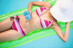 Beautiful woman relaxing on air bed in swimming poo Stock Photo