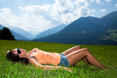 Beautiful woman is relaxing in the alps. On a meadow with the mountains in the background Royalty Free Stock Photos
